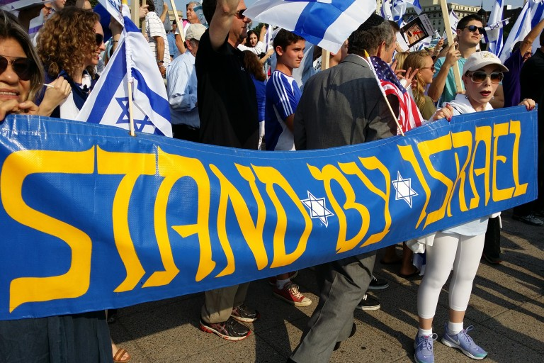 Photo of a parade banner displaying Stand by Israel