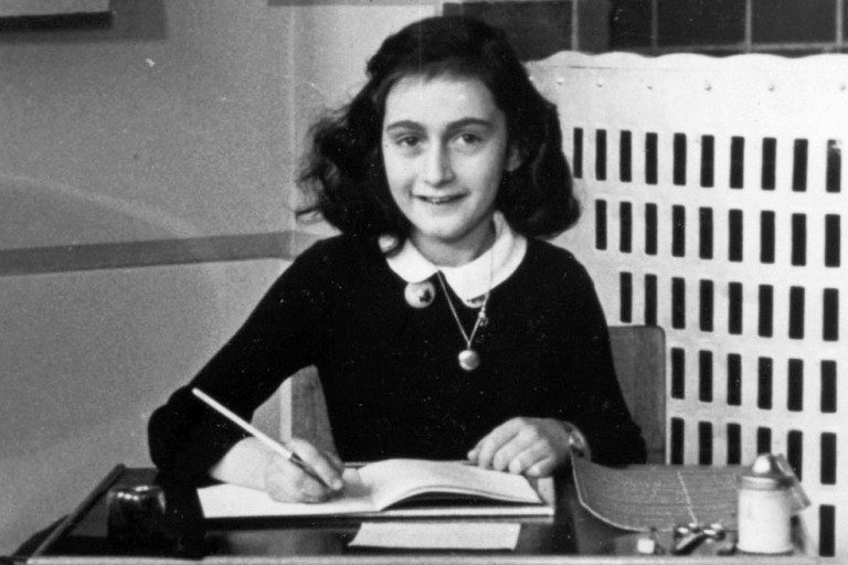 Photo of Anne Frank at her desk