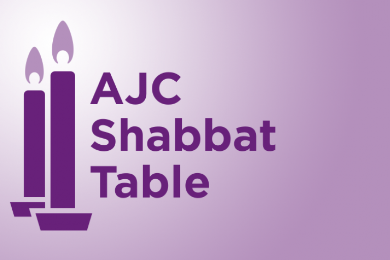 2 candlesticks on a light purple background with the words AJC Shabbat Table