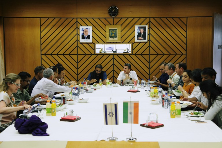 Delegation sitting in Israel. Indian and Israeli flag on the table.