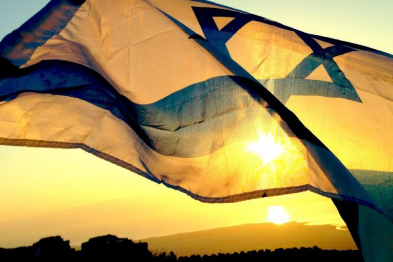 Photo of Israeli flag waving with a sunset in the background