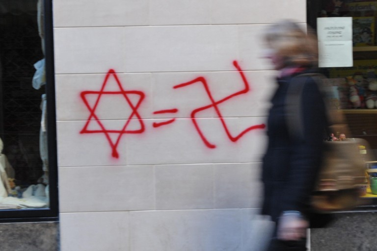 Photo of a Star of David, an equal sign, and a Swastika graffiti-ed on a wall