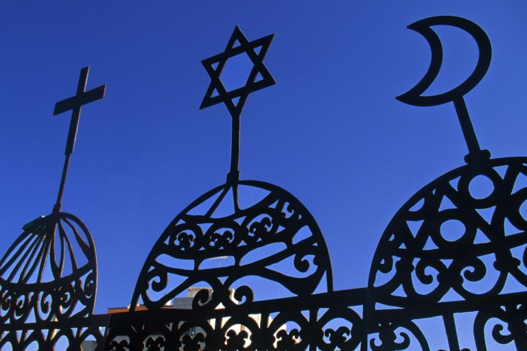 Photo of three religious symbols - a Cross, Jewish Star, and crescent moon.