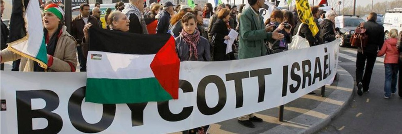 Photo of a BDS march with a large Boycott Israel banner