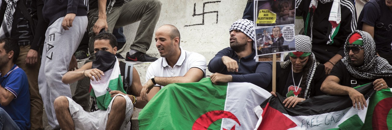 A group of extremist Muslims in Europe gathers around a statue with a swastika graffitted on it