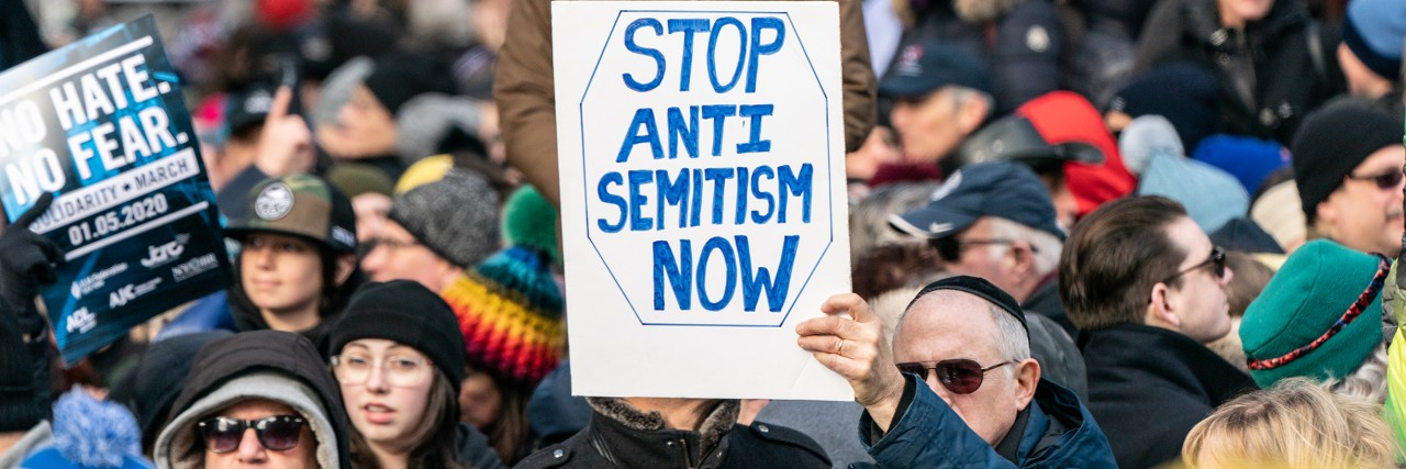 "Photo of a crowd and a man holding a sign saying ""Stop Antisemitism Now"""