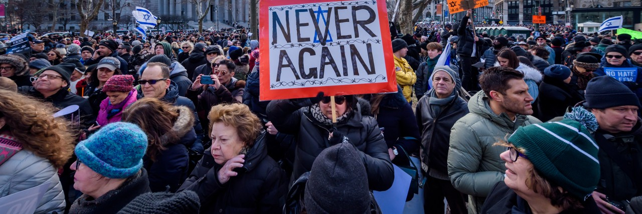 "Photo of a crowd and a woman holding a sign saying ""Never Again"""