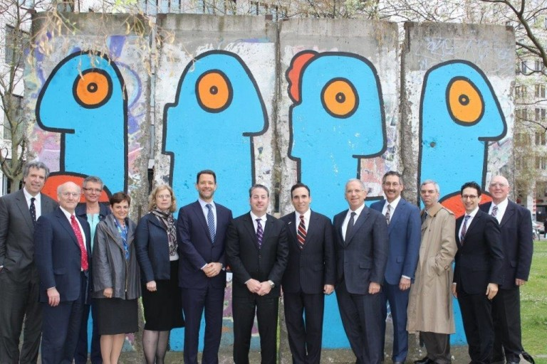 Photo of individuals on AJC-Adenauer Leadership Exchange Program standing in front of the Faces with Big Lips mural on a section of the Berlin Wall