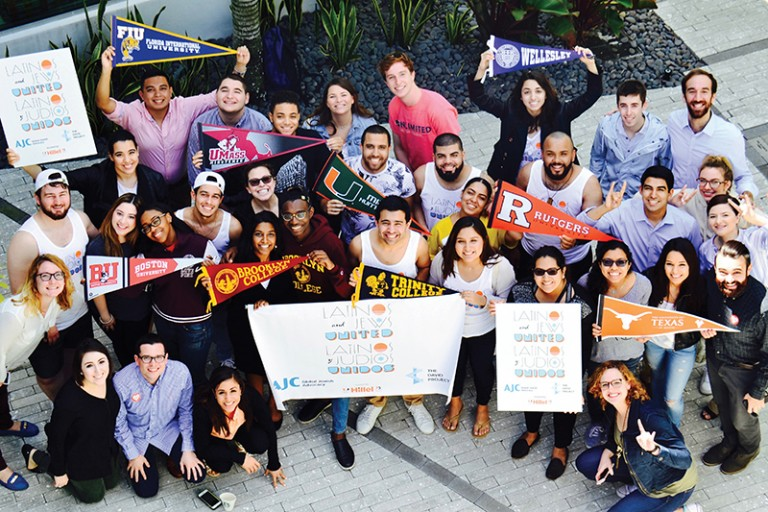Photo of Jewish and Latino student leaders from 10 U.S. universities gathering holding up flags from their respective schools including, FIU, UMASS, BU, Brooklyn College, Wellesley, Rutgers, UT, Trinity College, and University of Miami