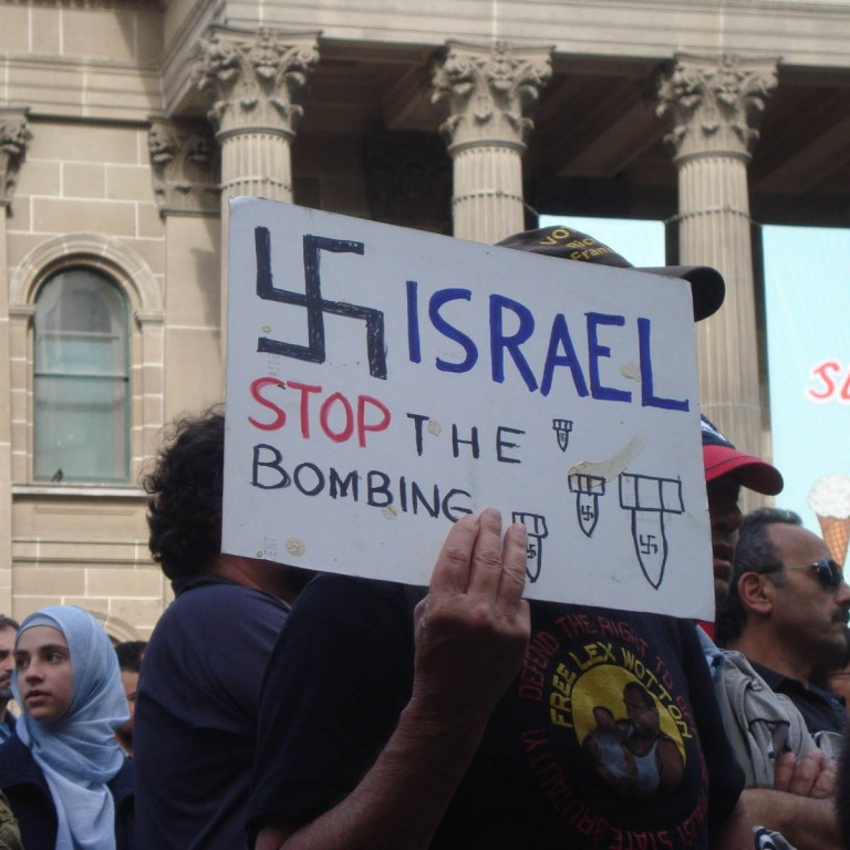 "Photo of a protest sign with a Swastika saying ""Israel stop the bombing"""