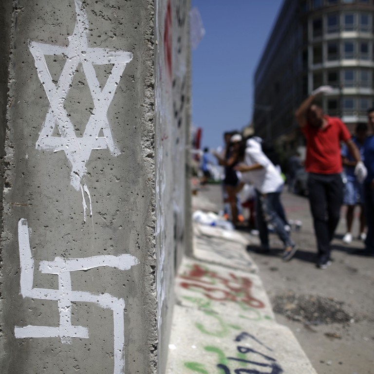 Photo of graffiti of a Star of David and a Swastika