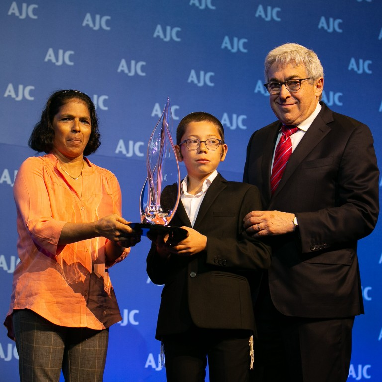 Photo of Sandra Samuel receiving the AJC Moral Courage Award with Former-AJC President Stanley M. Bergman and Moshe Holtzberg