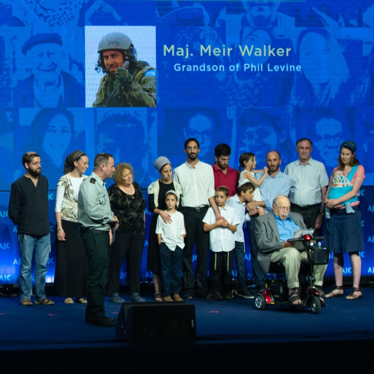 Photo of Phil Levine, his grandson Maj. Meir Walker, and their family onstage at AJC Global Forum 2018