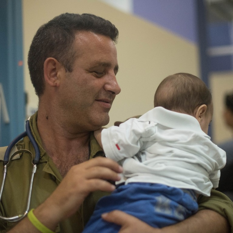 Photo of Israeli doctor holding a Syrian baby