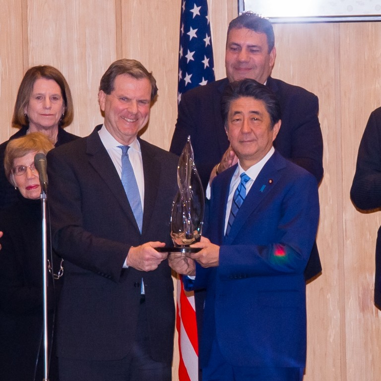 Photo of AJC CEO David Harris presenting AJC Light Unto Nations Award to Japanese Prime Minister Abe Shinzo