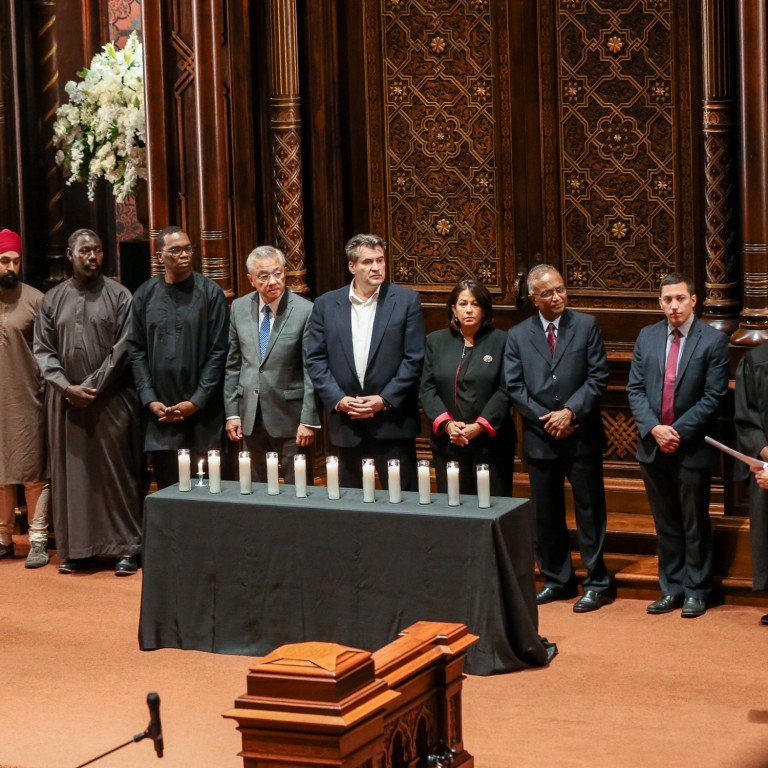 Members of AJC NY's Community of Conscience stands together behind candles at the Day of Action Against Antisemitism