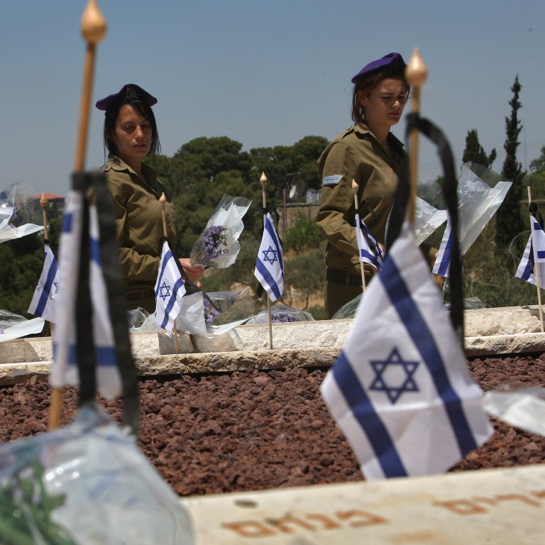 Photo of Israeli Soldiers at a memorial with Israeli flags