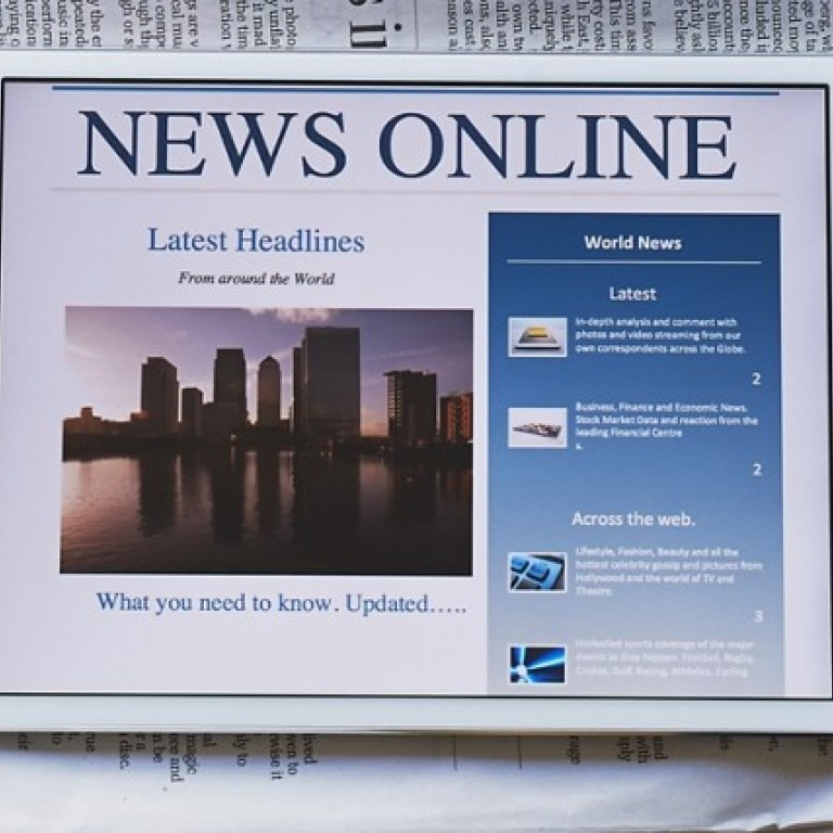 "iPad saying ""News Online"" with a newspaper behind"