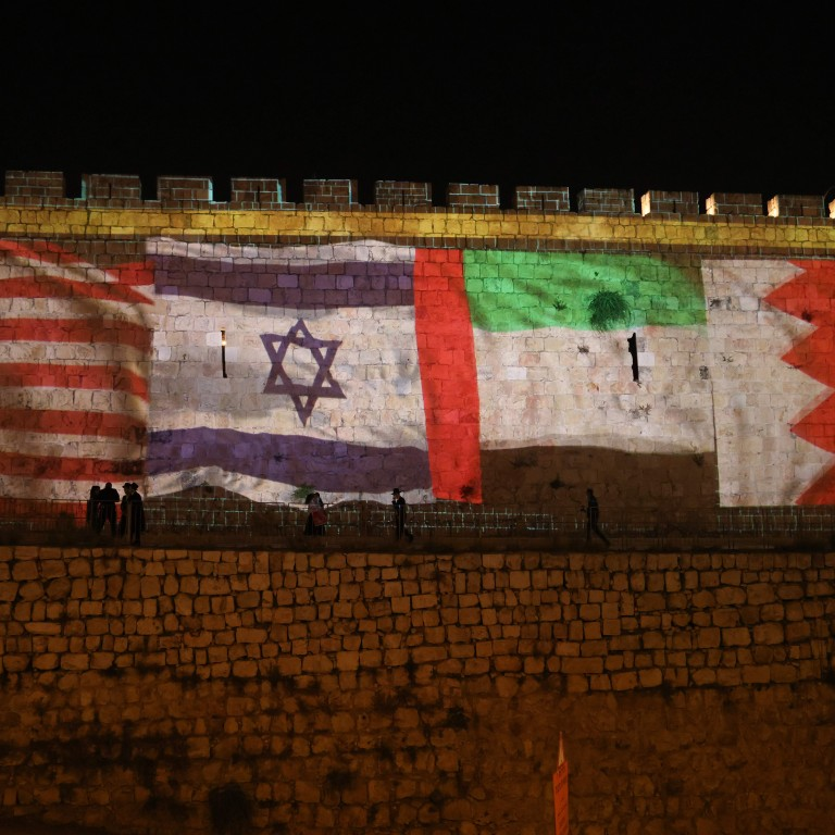 Flags of the US, Israel, UAE, and Bahrain alight the wall of the Old City of Jerusalem