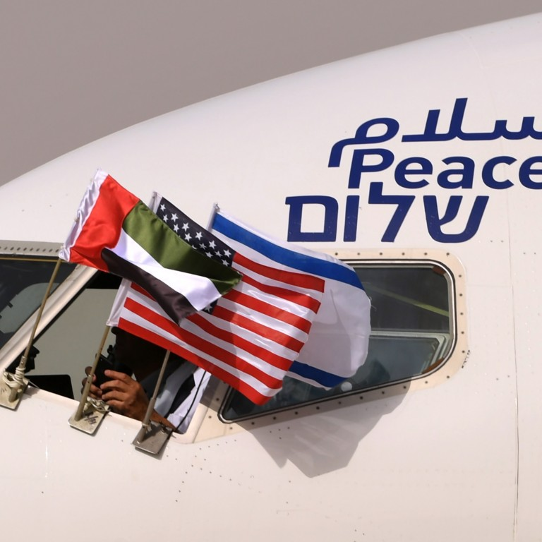 "The Emirati, Israeli and US flags are picture attached to an air-plane of Israel's El Al, adorned with the word ""peace"" in Arabic, English and Hebrew"