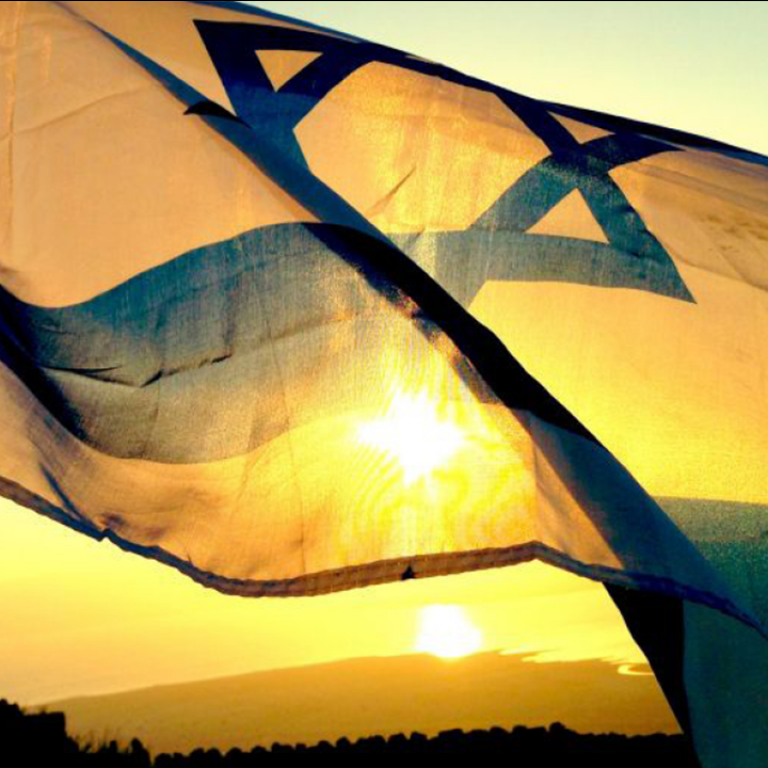 Israeli flag waving in the wind with sunrise in background